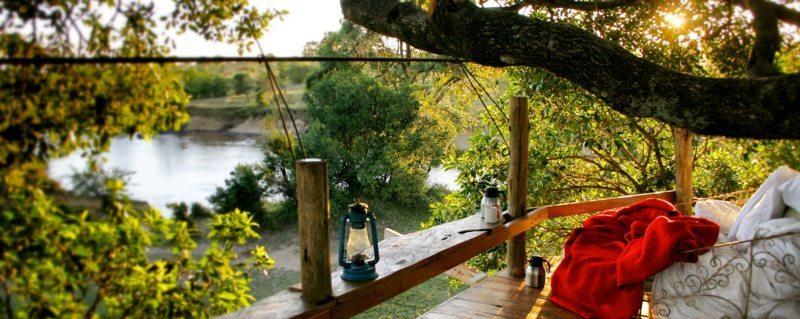A Masai Mara treehouse deck affords spectacular views over the Mara River..