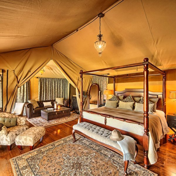 The tents at Sand River Masai Mara are elegantly luxurious, from the four-poster bed to the Persian carpet, velvet bed-end bench and crystal decanter. © Elewana Collection