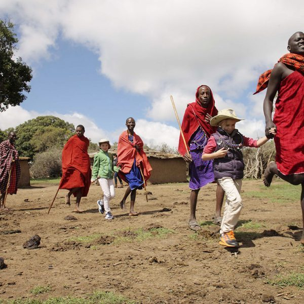 The Maasai interact warmly with children during cultural visits. © &Beyond