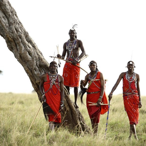Four strapping Maasai warriors show off their traditional headgear, beads and red dress in the Masai Mara. © &Beyond