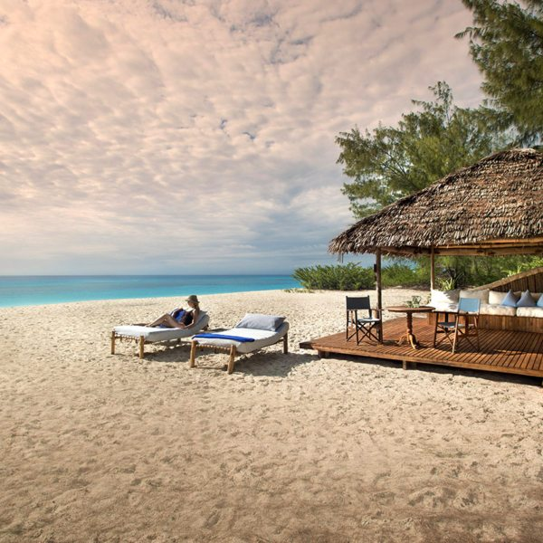 Mnemba Island invites lazy days on beach loungers. © &Beyond