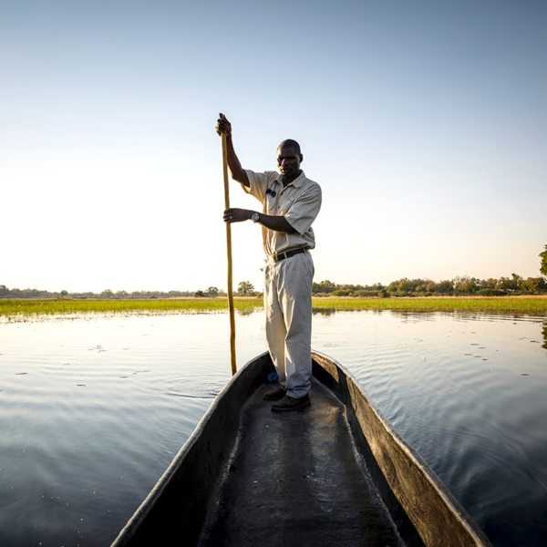 Mekoro are propelled through the shallow Okavango Delta by standing in the stern and pushing with a pole, similar to punting. © Sanctuary Retreats