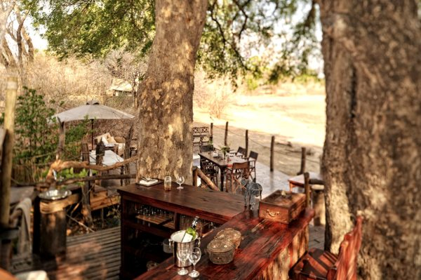 Kanga Camp's dining area is nestled among shady trees. © African Bush Camps