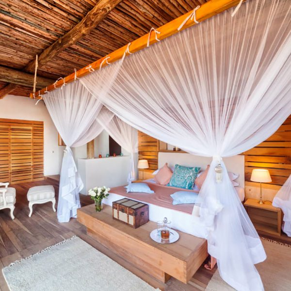 The beds at Saruni Ocean are enfolded with flowing mosquito nets. © Saruni