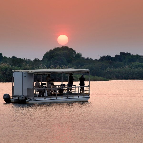 A sundowner boat cruise is a must when staying at Matetsi River Lodge. © &Beyond