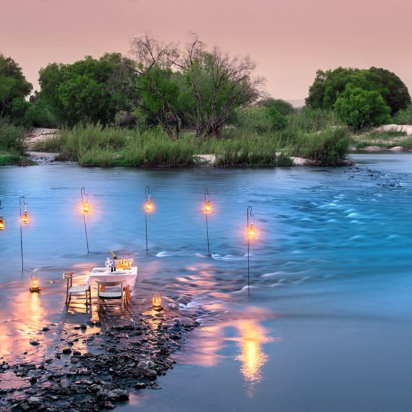 Enjoy a private dinner right at the water's edge at Matetsi River Lodge. © &Beyond