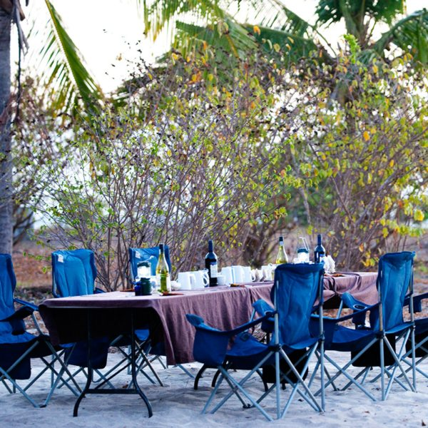 You'll dine comfortably at tables when island hopping in the Quirimbas. © Ibo Island Lodge