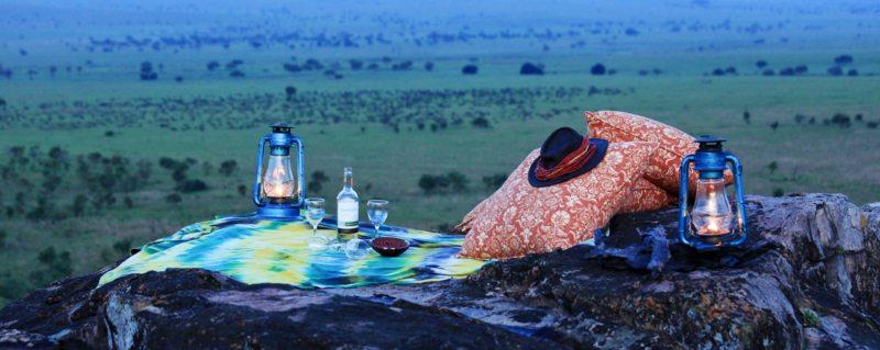 Luxury Uganda Safari | Sip sundowners on a rocky ridge near Apoka Safari Lodge.
