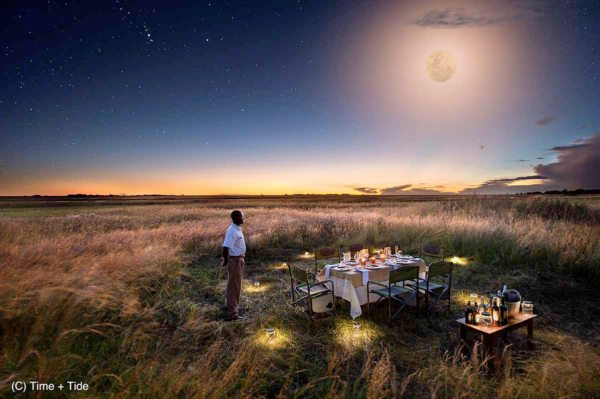 Dine under the African moon at King Lewanika Lodge. © Time + Tide