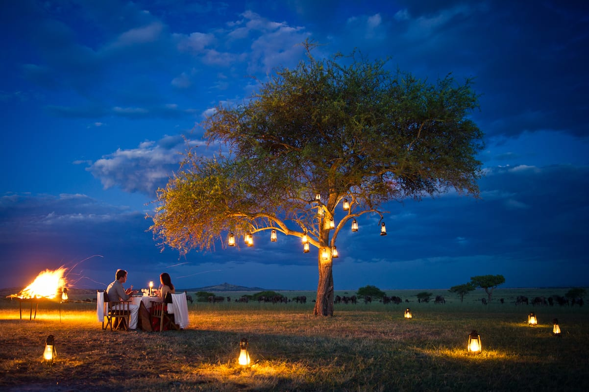Dinner by lantern light is a safari specialty. © Singita
